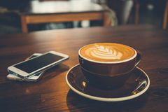 A cup of coffee on wooden surface.  Stock Images