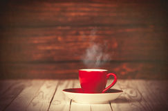 Cup of coffee on wooden table and background. Stock Photography