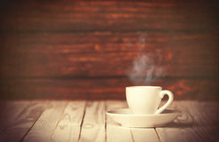 Cup of coffee on wooden table and background. Stock Photos