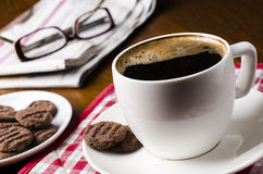 Cup of coffee on a wooden table with biscuits, glasses and newspaper Stock Images