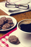 Cup of coffee on a wooden table with biscuits, glasses and newspaper Stock Photos