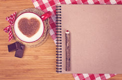 Cup of coffee on wooden table with blank paper and pencil. Cup of coffee with cinnamon heart on wooden table with blank paper, wooden pencil and red and white Stock Photo