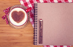 Cup of coffee on wooden table with blank paper and pencil, St. V. Cup of coffee with cinnamon heart on wooden table with blank paper, wooden pencil and red and Royalty Free Stock Images