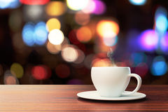 Cup of coffee on a wooden table and a blurred backdrop Royalty Free Stock Image