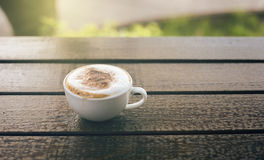 Cup of coffee on wooden table with blurred background,warm tone picture,filtered image,selective focus,light effect added.  stock photography