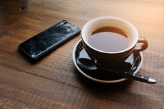 A Cup of coffee on a wooden table in the cafe. Near the phone. Coffee-break. The concept of food, business, entrepreneurship. royalty free stock images