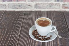 Cup of coffee on a wooden table, with cocoa powder forming a heart on the foam. White cup of coffee on a wooden table, with cocoa powder forming a heart on the royalty free stock images