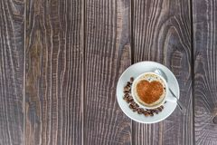 Cup of coffee on a wooden table, with cocoa powder forming a heart on the foam. White cup of coffee on a wooden table, with cocoa powder forming a heart on the royalty free stock photos