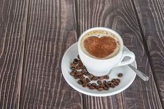 Cup of coffee on a wooden table, with cocoa powder forming a heart on the foam. White cup of coffee on a wooden table, with cocoa powder forming a heart on the stock photography