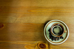 A cup of coffee on a wooden table. A cup of espresso  coffee with beans on a wooden table Royalty Free Stock Photos