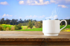 Cup of coffee a wooden table in front of spring landscape Stock Photography