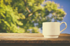 Cup of coffee a wooden table in front of tress background Stock Images