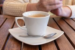 Cup of coffee on a wooden table and hands of an elderly woman behind. royalty free stock image