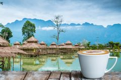 A cup of coffee on the wooden table by the lake. With hut and mountains background stock photo