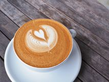 Cup of coffee on the wooden table with latte art. Stock Photo