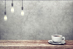 Cup of coffee on wooden table near concrete wall Stock Images