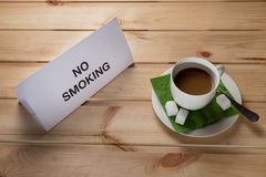 A cup of coffee on a wooden table with a note no smoking royalty free stock photo