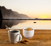 Cup of coffee on wooden table by ocean Royalty Free Stock Image