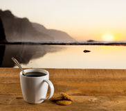 Cup of coffee on wooden table by ocean Royalty Free Stock Photos
