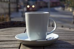 Cup of coffee on a wooden table outdoors royalty free stock photo