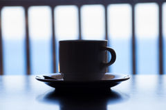 Cup of coffee on wooden table over sea view Royalty Free Stock Photography