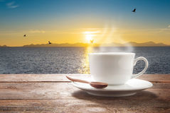 Cup of coffee on a wooden table at sea view Stock Photos