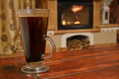 Cup of coffee on wooden table. Still life ahead of fireplace Stock Photo