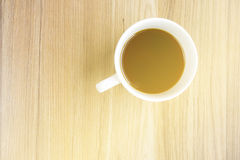 Cup of coffee on wooden table with sunlight from window Stock Image
