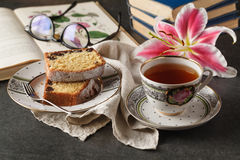 Cup of coffee on wooden table. Vintage books in the background stock images