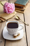 Cup of coffee on wooden table. Vintage books in the background Royalty Free Stock Image