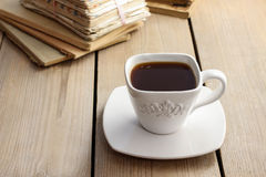 Cup of coffee on wooden table. Vintage books in the background Royalty Free Stock Images