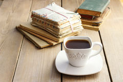 Cup of coffee on wooden table. Vintage books and pile of letters Stock Photos