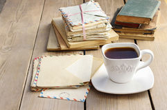 Cup of coffee on wooden table. Vintage books and pile of letters. In the background Stock Image