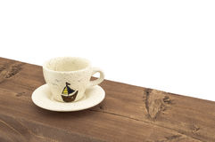 A cup of coffee on a wooden table. On a white background Stock Image
