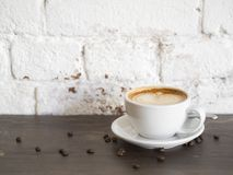 Cup of cappuccino on wooden table with white brick wall background. royalty free stock photos