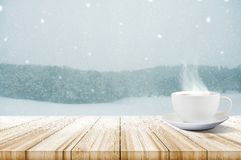Cup of coffee on wooden table with winter snowfall covered fores Royalty Free Stock Photos