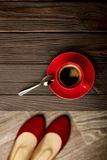 Cup of coffee on a wooden table and womens shoes. Stock Image