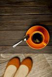 Cup of coffee on a wooden table and womens shoes. Royalty Free Stock Images