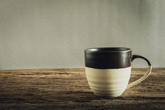 Cup of coffee on wooden tabletop against grunge wall Royalty Free Stock Image