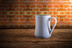 Cup of coffee on wooden tabletop against grunge wall Stock Images