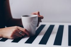 A cup of coffee on wooden texture. A cup of coffee in hands. Morning time Royalty Free Stock Photography