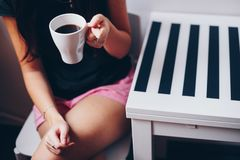 A cup of coffee on wooden texture. A cup of coffee in hands. Morning time Stock Images