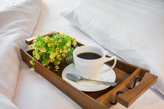 Cup of coffee in wooden tray on comfortable bed with pillow Stock Photos