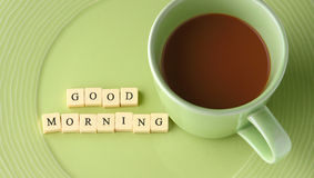 Cup of coffee with words good morning. On green dish Royalty Free Stock Photo
