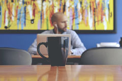 Cup of coffee and worker in office Royalty Free Stock Photo