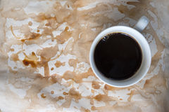 Cup of coffee on worn paper. With coffee stains and rough royalty free stock image