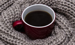 Cup of coffee wrapped in scarf. A cup of coffee wrapped in a warm scarf with a large viscous Royalty Free Stock Photo