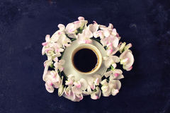 Cup of coffee, wreath sweet peas, black shabby table Royalty Free Stock Image