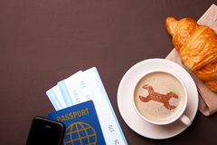 Cup of coffee with wrench on the foam. Coffee break or delay for technical reasons. Cup of coffee and croissant, plane tickets royalty free stock images