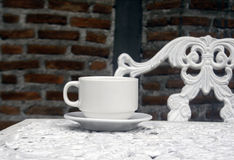 Cup of coffee on wrought iron garden table Royalty Free Stock Photo